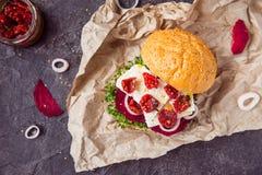 Den Vegitarian hamburgaren med betaskivor, microgreen groddar, tofuost, torkade tomater och löken på kraft packepapper på den mör Arkivfoton