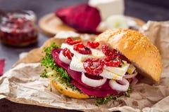 Den Vegitarian hamburgaren med betaskivor, microgreen groddar, tofuost, torkade tomater och löken på kraft packepapper på den mör Royaltyfri Foto