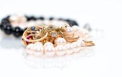 Den verkliga guld- jewleryen, diamanter, ädelstenar, cirklar som är neckless med pärlor, stänger sig upp skott royaltyfri fotografi