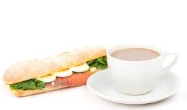 Den verkliga smörgåsen med den rökte laxen, ägg och gräsplan och kuper av ett kaffe på en vitbakgrund Royaltyfri Fotografi