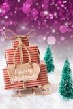 Den vertikala julsläden på purpurfärgad bakgrund, smsar lycklig helg Arkivbild