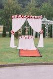 Den vertikala sikten av bröllopbågen dekorerade med röda och vita rosor Royaltyfri Foto