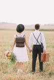 Den vertikala sikten av den tillbaka sidan av nygifta personerna som tycker om tiden i det soliga fältet Bruden rymmer Fotografering för Bildbyråer