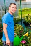 Den vertikala ståenden av en man med bevattna kan i en trädgård Arkivfoton