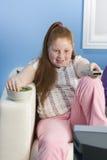 Den överviktiga flickan med fjärrkontroll äter söt mat på soffan Royaltyfria Bilder