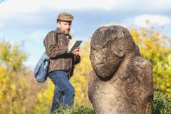 Den vetenskapliga historiker beskriver stenskulptur på kullen royaltyfri bild