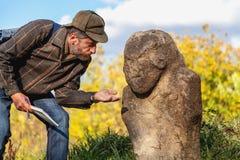 Den vetenskapliga historiker beskriver stenskulptur på kullen royaltyfria foton