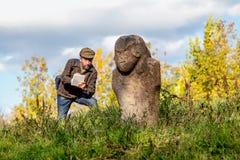 Den vetenskapliga historiker beskriver stenskulptur på kullen arkivbilder