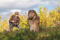 Den vetenskapliga historiker beskriver stenskulptur på kullen royaltyfri foto
