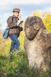 Den vetenskapliga historiker beskriver stenskulptur på kullen royaltyfri fotografi