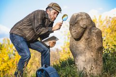 Den vetenskapliga historiker undersöker till och med förstoringsglasstenscu fotografering för bildbyråer