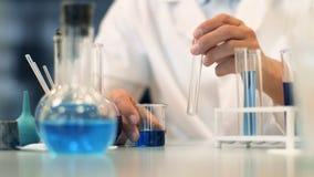 Den vetenskapliga laboratoriumforskaren utför prov med blå flytande close upp stock video