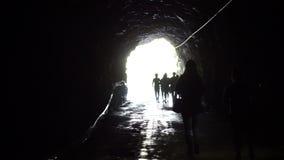 Den videopd konturn av folk går till och med den mörka tunnelen in i det glödande slutet Frihets- och lösningsbegrepp stock video
