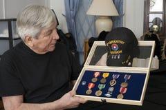 Den Vietnam veterinären ser över hans medaljer Arkivbild