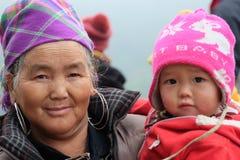 Den vietnamesiska etniska H'Mong gamla kvinnan med behandla som ett barn i traditionella dräkter Arkivfoto