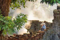 Den vietnamesiska kvinnan som arbetar bland, fördärvar av gamla byggnader, ton royaltyfri fotografi