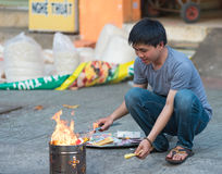 Den vietnamesiska mannen bränner votive offerings Fotografering för Bildbyråer
