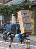 Den vietnamesiska mannen kör kylen på motorcykeln Arkivbild