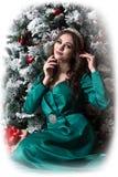 Den Vignetted bilden av en härlig modellflicka i en grön klänning nära en dekorerad julgran håller hennes händer på hennes framsi royaltyfri fotografi