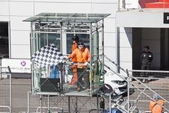 Den vinkande kontrollflaggan i luft på loppet avslutar sig Royaltyfri Foto