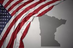 Den vinkande nationsflaggan av USA på en grå färgminnesota stat kartlägger bakgrund arkivfoton