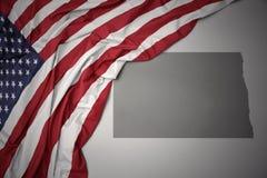 Den vinkande nationsflaggan av USA på en grå färgNorth Dakota stat kartlägger bakgrund royaltyfria bilder