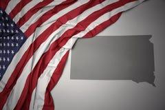 Den vinkande nationsflaggan av USA på en grå färgSouth Dakota stat kartlägger bakgrund royaltyfri foto