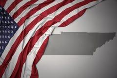 Den vinkande nationsflaggan av USA på en grå färgtennessee stat kartlägger bakgrund Royaltyfri Foto