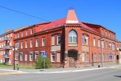 Den vinkelformiga byggnaden för forntida tegelsten på korsning av gator Arkivbilder