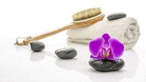 Den violetta orchiden med brunnsortstenar, borstar och handduken Royaltyfri Fotografi