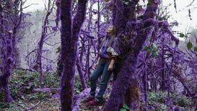 Den violetta sagaskogflickan lutar mot etttäckt träd i en mystisk purpurfärgad skog som ut zoomar fantasi lager videofilmer