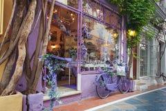 Den violetta souvenir shoppar fasaden som dekoreras med den violetta cykeln som parkeras nära väggen Arkivbilder