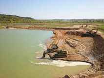 Den Vislock floden, Polen - kan 2, 2018: Grävskopan laddar dumper med jord Land arbetar i villebrådet av flodgrus extract arkivbild