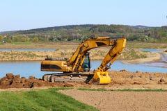Den Vislock floden, Polen - kan 2, 2018: Grävskopan laddar dumper med jord Land arbetar i villebrådet av flodgrus extract royaltyfri foto