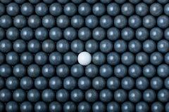 Den vita airsoftbollen är bland många svarta bollar Bakgrund av 6mm bbs Fotografering för Bildbyråer