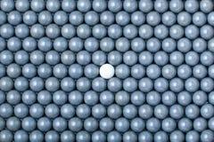 Den vita airsoftbollen är bland många svarta bollar Bakgrund av 6mm bbs Royaltyfri Bild
