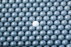 Den vita airsoftbollen är bland många svarta bollar Bakgrund av 6mm bbs Royaltyfria Foton