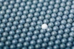 Den vita airsoftbollen är bland många svarta bollar Bakgrund av 6mm bbs Royaltyfri Fotografi