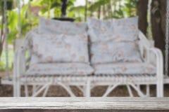 den vita bänken för rottinggnäggandegunga med blått dämpar och kudde in Royaltyfri Fotografi
