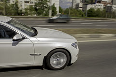 Den vita bilen går snabbt till staden Fotografering för Bildbyråer