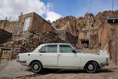 Den vita bilen på bakgrunden av stenar staketet av byn av Kandovan Tabriz Iran arkivfoto