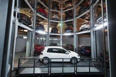 Den vita bilen på parkeringsplats med det automatiserade bilparkeringssystemet Royaltyfria Bilder