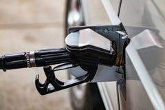 Den vita bilen tankas till en bensinstation, ett tanka vapen i fet Arkivfoto