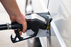 Den vita bilen tankas till en bensinstation, ett tanka vapen i fet Fotografering för Bildbyråer