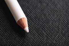 Den vita blyertspennan för fransk manikyr på en svart texturerade bakgrund Royaltyfria Bilder