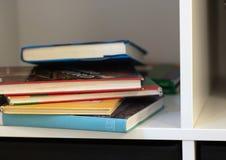 Den vita bokhyllan och flera böcker som ligger i förvirring arkivbild