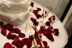 Den vita bröllopstårtan med den röda rosen langer Arkivfoto