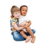 Den vita brodern som kramar svart, behandla som ett barn systern Royaltyfria Bilder