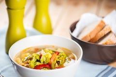 Den vita bunken av grönsaksoppa, bröd, saltar och pepprar Arkivfoto
