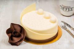Den vita chokladkakan och steg med kaffe på tabellen Royaltyfri Foto
